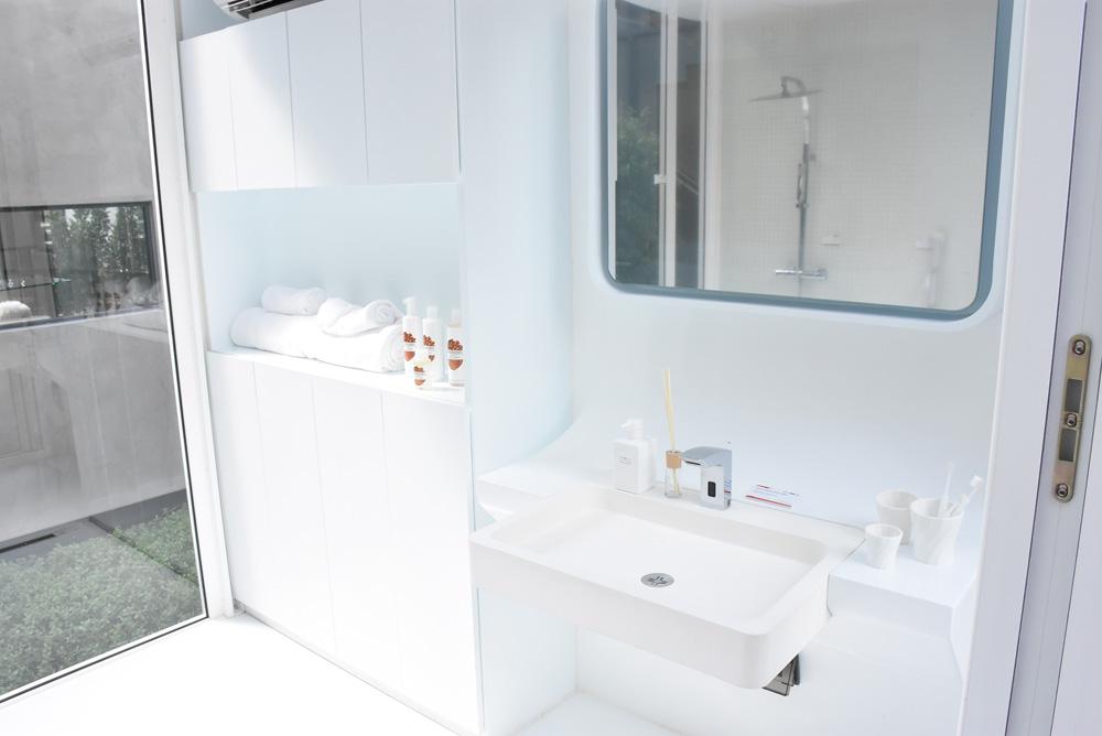 ห้องน้ำสีขาวตกแต่งด้วยอ่างล้างหน้าที่มีผิวสัมผัสเป็นยางเพื่อป้องกันอันตราย